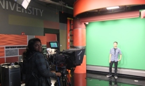A Senn student performs in front of  a green screen at Loyola's School of Communication. Loyola photo.